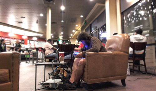 A man playing his Xbox in Starbucks.