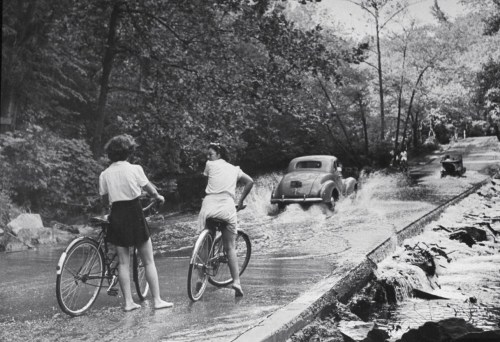 Hans Wild, Bicyclists waiting as an automobile drives through water running over a roadway in Rock Creek Park, Washington, DC, USA, September 1945.