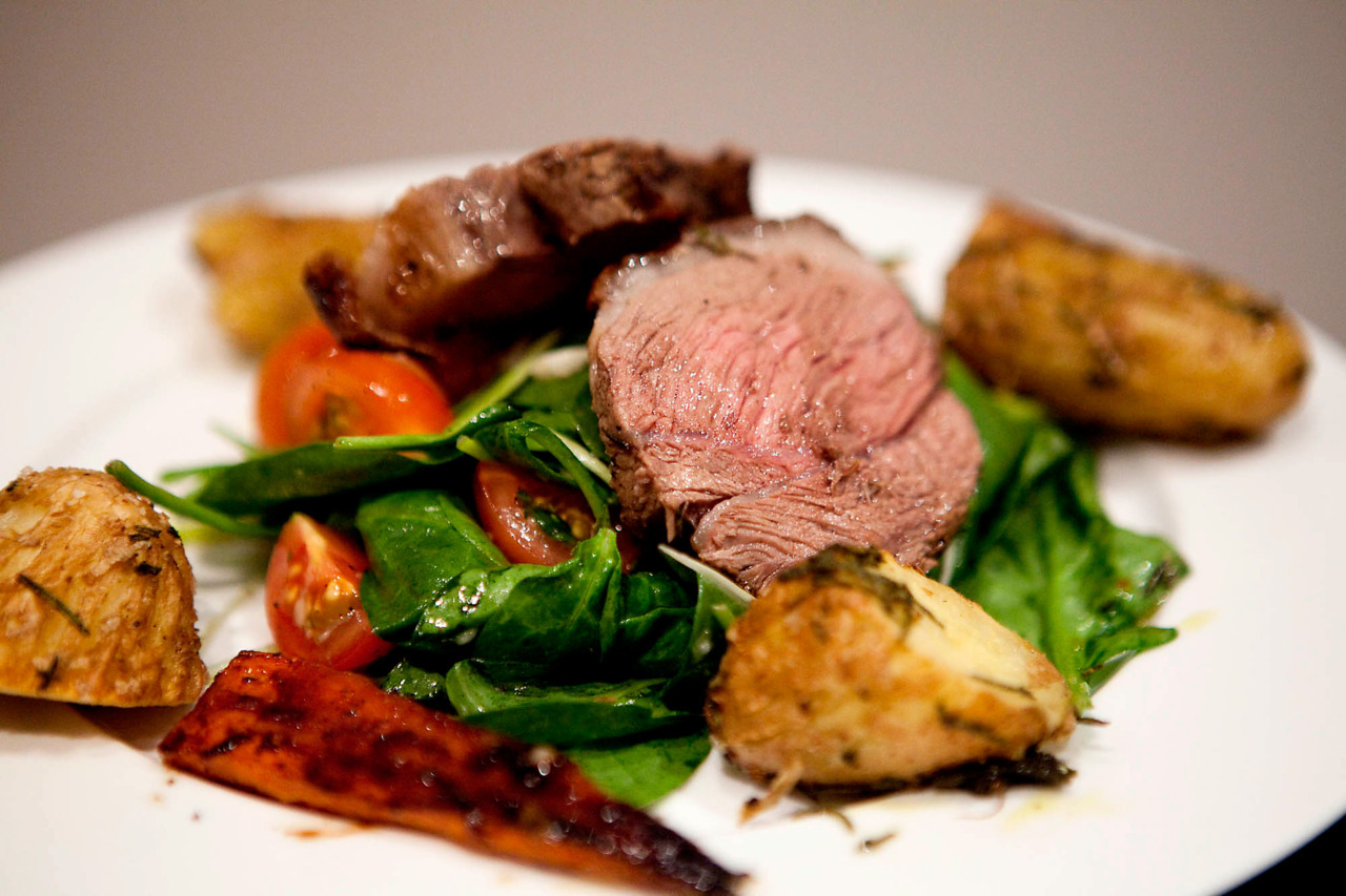 Lamb Rump Roast with Herb Roasted Potatoes and Spinach Salad Hands down, this is the best lamb I've ever eaten.  As part of the endless amount of meat I picked up from the market, I grabbed 2 lamb rumps and marinated them for 24 hours before cooking them.  It was quite easy to do, since I just put it together Sunday night, and then could throw it in the oven on Monday after work.  The salad was simple, and the potatoes I cooked with some of the reserved duck fat from the weekend.  You can buy it in the shop, but I just skimmed it from the bottom of the pan and put it in a container. Ingredients (lamb): 2 lamb rumps (think fairly large single serves… with leftovers) 1/2 cup thyme, roughly chopped 1/2 cup rosemary, roughly chopped Juice of half a lemon 3 garlic cloves, diced 3-4 tablespoons of olive oil Salt and pepper Toss everything together and marinade for at least a few hours to overnight.  It could probably even go 2 days.  Remove lamb from marinade, getting off the herbs, and set aside.  Get an oven-proof pan nice and hot, and sear the fatty side of the lamb for about 5 minutes, until it's starting to get really brown and burned.  This is going to get the lamb all sorts of juicy while it's cooking.  Flip it over, drizzle with a bit of olive oil (I also added some carrots, but I don't think it did anything for the lamb, they were just going off and needed eating), and bake for 30 minutes at 200C / 375F.  Remove, let rest for 5 minutes, and slice to serve.  If you want it to look really pretty, you can remove that fatty top bit, it's done its job. Ingredients (potatoes): 5-6 fingerling potatoes, skins scored with a fork, and chopped in half / thirds depending on size 1/2 cup chopped sage and rosemary Salt and pepper Heaping tablespoon of duck fat Combine the ingredients and bake for 40 minutes at 200C / 375F, flipping halfway through.