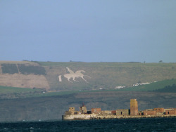 "King George III on Flickr.""The Osmington White Horse is a hill figure sculpted in 1808 into the limestone Osmington hill just north of Weymouth called the South Dorset Downs, within the parish of Osmington. The figure is of King George III, who regularly visited Weymouth, and made it 'the first resort', riding on his horse, and can be seen for miles around. … There is a legend that King George was offended that the figure was riding out of Weymouth — a sign that he was not welcome — and never returned."" ""In August 2011 pranksters added a 'horn' made from plastic sheeting to make the horse resemble a Unicorn. The Osmington White Horse is the only figure that is a case of both leucippotomy and gigantotomy"" - info from wikipedia. Surprised I spotted this in the distance from Portland - I couldn't see it too clearly to begin with, but my camera acted as a telescope. :)"