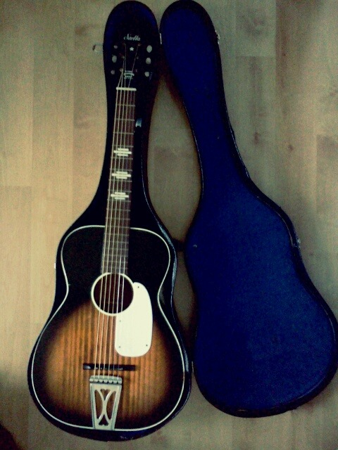 "Meet the latest addition to the family.It's a little Stella parlor-guitar circa 1965, found at a Goodwill in Kenosha, WI.It is also the first guitar/instrument that Christiana has ever bought for me. The bridge needs a little sanding to get the strings level with the neck, but once that's done she should play rather nicely. Either way, it sounds great. In honor of one of my favorite singers' recent departure, I've decided to name her ""Etta James."""