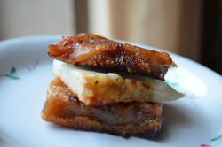 Day 75: Nian Gao Sandwich My nian gao (Chinese New Year cake) look like fleshy dead body parts of some unknown animal, but they're really just glutinous sticky rice pieces that taste really, really good in the morning. The charred bits add that extra oomph. Stuck in the middle is a piece of luo buo gao (turnip cake).