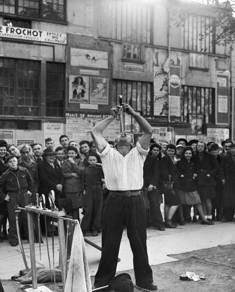 Ed Clark, A sword swallower performing on the streets of Paris, November 1945.