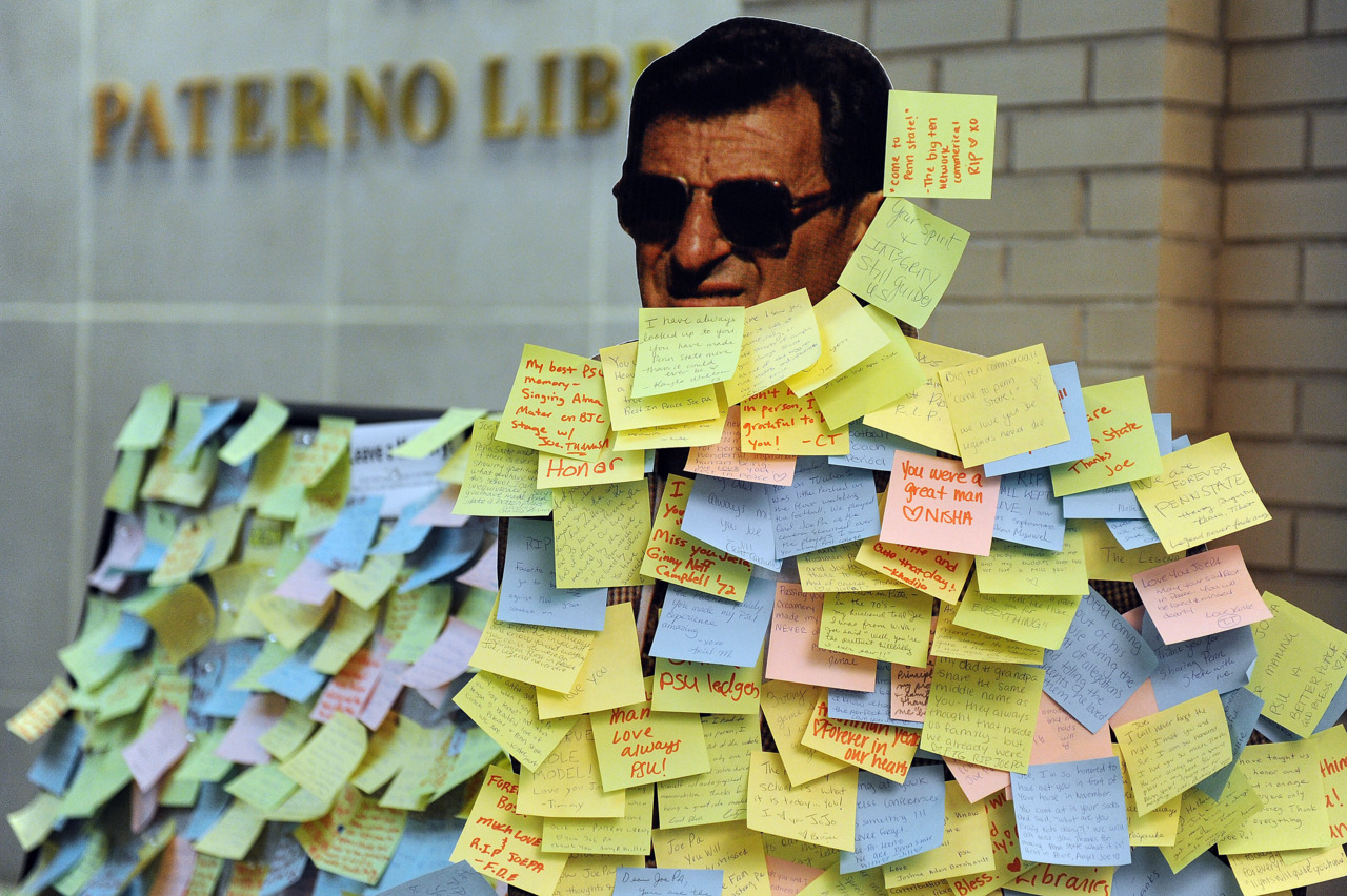 Students leave notes on a cardboard cutout of former Penn State Football coach Joe Paterno in the Pattee and Paterno Libraries on the campus of Penn State on January 24, 2012 in State College, Pennsylvania. Paterno, who was 85, died due to complications from lung cancer on Jan. 22. Photo by Patrick Smith/Getty Images