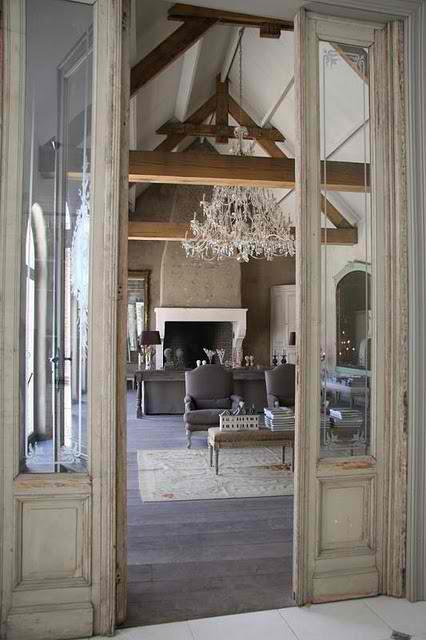 A beautiful old door with etched glass sidelights leads into a vaulted-ceiling living area, which is centered by a huge crystal chandelier (via Anything FRENCH…..Ooh la la)