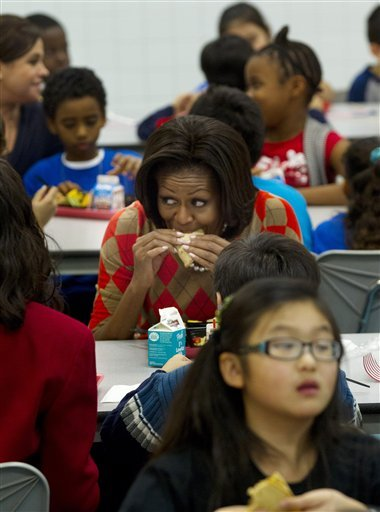Michelle Obama eating a taco: First lady Michelle Obama takes a bite of her turkey taco as she has lunch with school children at Parklawn Elementary School in Alexandria, Va. Obama's helping pitch some new rules for school lunches. (Photo by Pablo Martinez Monsivais/AP)