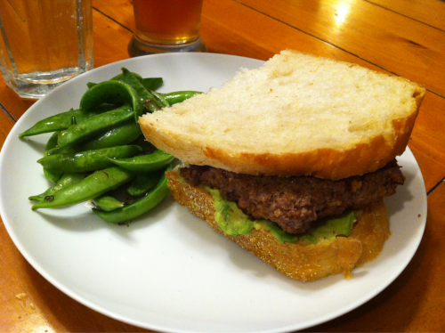 Dinner. Organic ground beef burger, with smeared avocado instead of mayo, and spicy mustard. On olive oil bread. Sugar snap peas from my Bountiful Baskets produce co-op, drizzled with a tiny bit of olive oil vinaigrette. And a Bear Republic Racer 5 IPA.