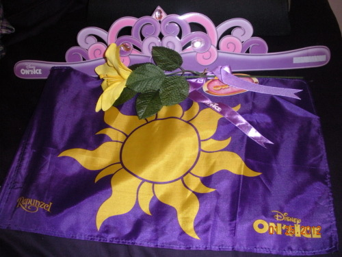 some of my Disney on Ice souvenirs, I HAD to get the  Rapunzel flag. The crown came with the bag of cotton candy (which is why it was 24 freakin dollars for 2 bags of it). The forbidden flower came with the program.
