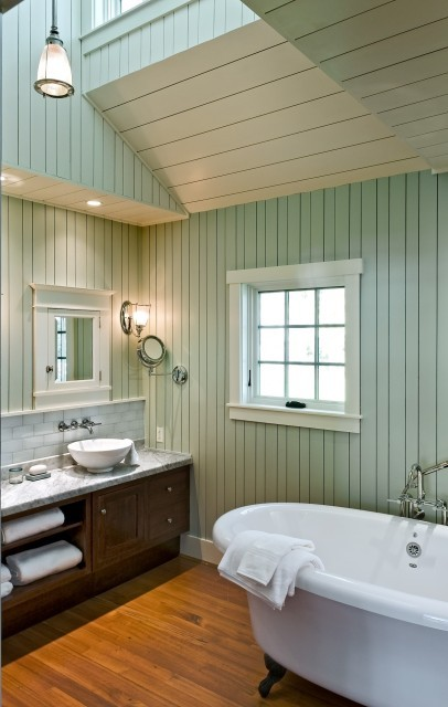 A charming cottage bathroom features a complex multi-vault ceiling, claw foot tub, and painted wooden beadboard walls. (via Whitten Architects)