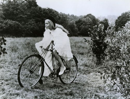 Margaret Leighton rides a bike.