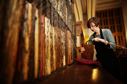 rhea137:  Dr. Rosemary Firman, librarian of Hereford Cathedral, uses a  conservation vacuum as she finishes cleaning one of the historic  manuscripts in the cathedral's peculiar Chained Library during the  annual spring clean on Jan. 24 in Hereford, England. The famous library contains 1,500 books, including 227  medieval manuscripts. Given the delicate state of the literary works,  specialists and trained volunteers must spend a week out of the year  cleaning the entire collection.   Chaining books for security was widespread in libraries from the  Middle Ages to the 18th century, and Hereford Cathedral's 17-century  Chained Library is the largest to survive with all its chains, rods and  locks intact. MNN's photos of the week
