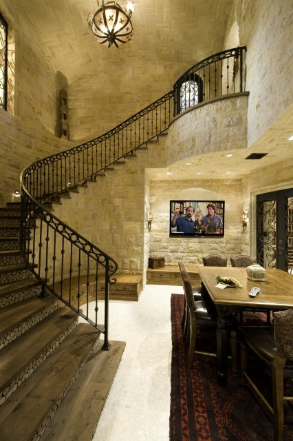 A combination wine cellar and home theater is accessed via a sweeping marble staircase with an iron railing (via Bliss Home Theaters & Automation, Inc)