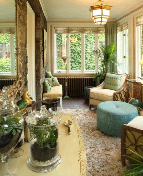 A bright and cozy sun room features abundant windows and a mix of plants and natural rattan furniture, with yellow accents the color of sunbeams. (via Karen Gallagher Interiors)