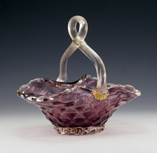 "(via Retro Art Glass: Vintage Venetian Glass Hand-Blown Optic Basket) Beautiful Venetian glass basket from mid-20th century Italy. Old sticker on base reads ""Genuine Venetian Glass Made in Murano Italy"".  This is a generic label from the 1940s to 1960s. The sticker is not directly attributed to one of the infamous mid-century Italian glass masters, but likely came from one of their studios.  Read more about Italian Glass. Hand-made in plum amethyst crystal with richly defined diamond pillow optic decor and applied colorless reeded handle and ruffled rim and base.  Gold leaf is spattered throughout the colorless glass.   The rim, handle and base ruffle were applied to the optic basket.  Well-made by a fine artist. In perfect condition.  Measures 7½"" tall, 7.75"" long, and 5.25"" wide. For the luxurious Easter basket!  Lovely eye-catching item with multiple uses; flowers, fruit, business cards, etc."