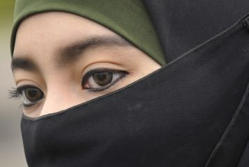 The Dutch government today promised to ban face coverings, including burqas or niqabs, by next year.
