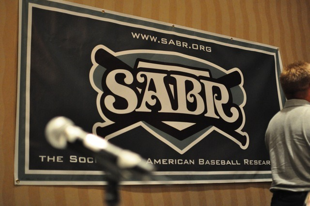 mightyflynn:  Today is SABR Day.  SABR [Society for American Baseball Research] members have a variety of interests, and this is reflected in the diversity of its research committees. There are more than two dozen groups devoted to the study of a specific area related to the game — from Baseball and the Arts to Statistical Analysis to the Deadball Era to Women in Baseball. In addition, many SABR members meet formally and informally in regional chapters throughout the year and hundreds come together for the annual national convention, the organization's premier event. These meetings often include panel discussions with former major league players and research presentations by members. Most of all, SABR members love talking baseball with like-minded friends. What unites them all is an interest in the game and joy in learning more about it.  - The SABR Story [excerpt]  I'm a proud member of the Halsey Hall Chapter of SABR.  Learn more about SABR and the benefits of membership here. (photo UmpBump.com)  Wow. This organization sounds very glorious. And I have less than three months left to take advantage of the Under 30 pricing…