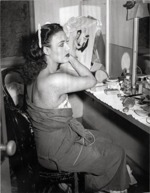 "Lena Horne snapped by Charles ""Teenie"" Harris doing her hair in her dressing room before a performance at the Stanley Theater in 1940s Pittsburgh."
