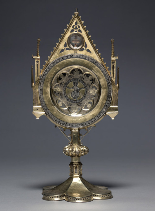 "Ostensorium with ""Paten of St. Bernward."" German (Lower Saxony [Hildesheim?]), ca. 1180-90 (paten); ca. 1350-1400 (monstrance). The Cleveland Museum of Art. From the Treasures of Heaven exhibit:  This unusual ostensorium (from the Latin ostendere: to show) was made to facilitate the display and veneration of ten relics, most prominent among them an elaborate liturgical paten—a shallow plate for the elevation of the Eucharist during Mass—associated with St. Bernward of Hildesheim (d. 1022), and a relic of the True Cross.  On the back, eight more relics are visible:  They're wrapped in silk and are identified—by an inscription on parchment accompanying the piece—as the remains of Saints Godehard, Nicholas, Auctor, Silvester, Servatius, John Chrysostom, Alexis, and Lawrence."