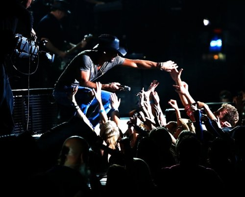 Tim McGraw reaching towards his fans in concert