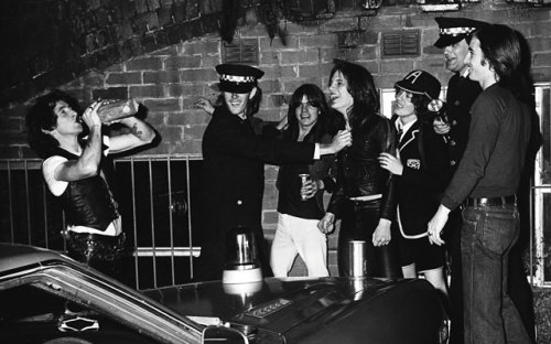 "Left to right: Bon Scott, an unidentified ""cop,"" Malcolm Young, Phil Rudd, Angus Young, AC/DC's then-manager George Browning, and Evans have a laugh and a drink during a March 1976 photo shoot for ""Jailbreak."" Photo by Philip Morris"