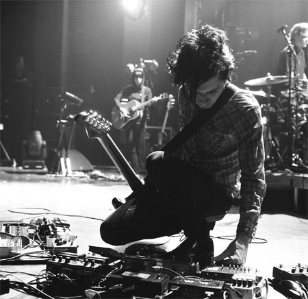 On tour with the Yeah  Yeah Yeahs' in 2009, Nick Zinner tweaks one of his three pedalboards  stocked with Line 6, Boss, Electro-Harmonix, Foxx, DigiTech, and other pedals (as well as a Voodoo Lab Pedal Power) as  rhythm guitarist Jessica Dobson looks on. Photo by David Belisle