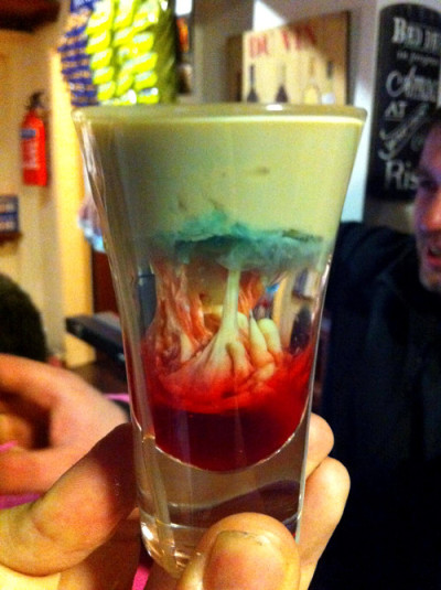 archiemcphee:  Feeling thirsty? This gruesome creation is a cocktail called the Alien Brain Hemorrhage. Here's how you make one: Fill a shot glass halfway with peach schnapps. Gently pour Bailey's Irish Cream on top. After the shot is almost full, carefully add a small amount of blue curacao. After it settles, add a small splash (or a few drops) of grenadine syrup. Photo by Martin Williams [via Neatorama]
