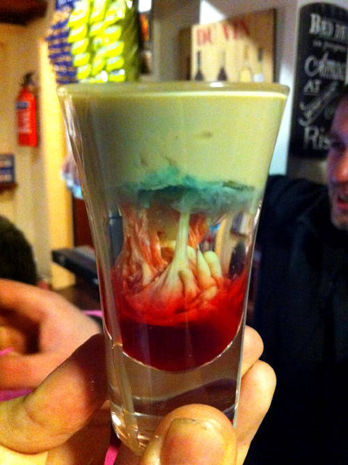 "This revolting thing is a cocktail called an ""Alien Brain Hemorrhage"":  ""To make an alien brain hemorrhage cocktail, fill a shot glass halfway  with peach schnapps. Gently pour Bailey's Irish Cream on top. After the  shot is almost full, carefully add a small amount of blue curacao. After  it settles, add a few drops of grenadine syrup."" Looks like it could be  improved with a couple lumps of dry ice."