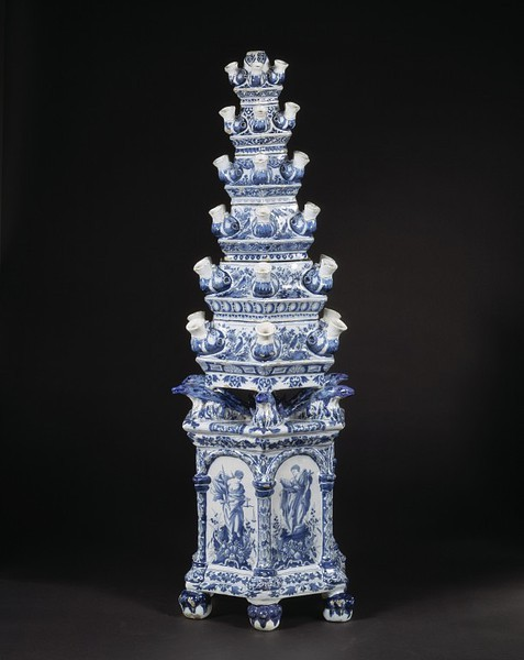 Flower pyramid Place of origin:  Delft, Netherlands (made)   Date:  ca. 1695 (made)   This flower vase originally consisted of a separate base and seven stackable tiers (one of which is now missing). Each tier could hold water and each of its six spouts could hold a few cut flowers. Although the idea of making a ceramic pyramid originated in The Netherlands, the shape of such monumental vases was probably derived from a Chinese pagoda. People The arms and motto of John Churchill (1650-1722) as Earl of Marlborough are incorporated in the painted decoration on the base of this object. Churchill held the title of Earl from 1689 until he became the 1st Duke of Marlborough in 1702. The motto 'FIEL PERO DESDICADO' ('Faithful, though unfortunate') is accompanied by symbolic figures of Justice, Faith, Charity and Wisdom. Mary II (1662-1694) introduced the fashion for Dutch delftware to England when she returned from The Netherlands in 1689. Mary herself ordered large amounts of wares from Adrianus Kocx, proprietor of the prestigious 'Greek A' factory in Delft from 1686 to 1701. At the time of her death, she owed him £122 14s 9d for 'Dutch China or ware'. William III used splendid Delft pieces as royal gifts to his English nobles. http://collections.vam.ac.uk/item/O77966/flower-pyramid/