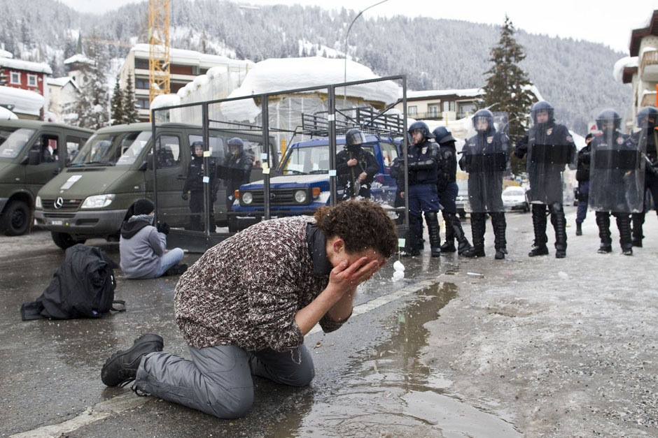 An anti-WEF demonstrator uses water from a puddle to wash his eyes after he was sprayed with tear gas by Swiss Riot Police during a protest against the ongoing World Economic Forum in Davos January 28, 2012. [Credit : Miro Kuzmanovic/Reuters]