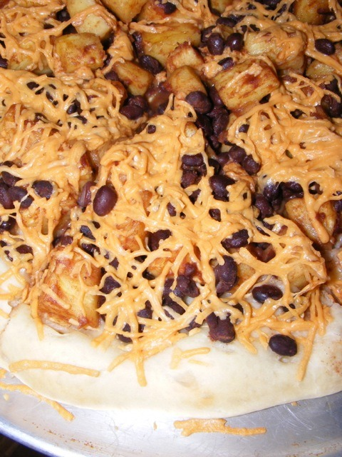 Pineapple Black Bean PizzaI like turning other dishes into pizza so I decided to try this, which I usually eat with rice. My homemade crust is topped with pineapple & black beans sprinkled with cinnamon and the whole thing is covered in cheddar Daiya. This is my 3rd entry for the Vegan Pizza Day giveaway. Made in the USA by me :) I also write The Vegan Kitchen blog [OMG, I swear those pineapples look like tots! Or maybe I just have tots on the brain! Whatever, looks delish! Thanks for sharing, twolightsabovethesea! - ed.]