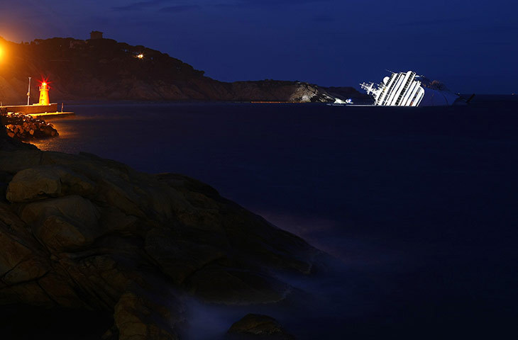 Giglio, Italy The wreck of the cruise liner Costa Concordia lies outside the harbour at dusk (via guardian.co.uk)