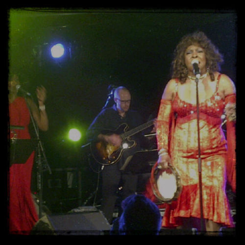 "Martha Reeves and the Vandellas @ The Arches During a period where it is near impossible to read the latest music news without the words ""reformed"" and ""reunion tour"" making an appearance, one of the biggest fears about classic artists taking to the stage for one final fling is that over time the voice will have naturally deteriorated. It is with credit then to Martha Reeves that she has kept on performing for over fifty years without falter and at the remarkable age of seventy, could out perform any number of today's younger generation. Taking to the stage in a dazzling red dress, Miss Reeves was as glamorous and as sassy as ever as she effortlessly enchanted the audience with hit after glorious hit. As for the minority who were initially weary of letting loose, that was all pushed aside as soon as the unmistakable drums of Nowhere to Run kicked in. Jimmy Mack was a particular highlight as Martha and her wonderful band took the audience on a thrilling journey through some of the most iconic Motown and pop songs to have ever been produced. Songs such as Love (Makes Me Do Foolish Things) and Come and Get These Memories continued to cement her reputation as one of the best in the ""business"", continuously reminding the adoring audience just how influential and important the music of Martha Reeves and the Vandellas was and still is today. As if that wasn't enough, Martha and her band performed (Love is Like a) Heatwave and Dancing in the Street back to back, almost tearing the roof off a packed out Arches in the process. It's not every day you get to see such an iconic and influential figure of Motown perform in your hometown, let alone witnessing them perform a blistering and remarkable set of classic songs forty to fifty years after their release. But when that day does come, it is one of the most memorable and overwhelming days imaginable."