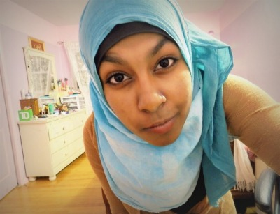 "Hijab Photo Competition (HPC) IIContestant #26: Siyma Karim from United States Reason for why your photo represents ""A True Hijabi: Allah tells us in surah nur, ayah 30-31 ""…and to draw their veils all over Juyubihinna (i.e. their bodies, faces, necks and bossoms)…"" the scarf covers my bossoms and it's worn with a long (maxi) cardigan over a black maxi dress. I hope that proper hijab?"