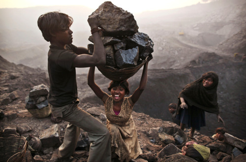 A young woman stumbles as she tries to carry a large basket of coal as they illegally scavenge at an open-cast mine in the village of Bokapahari, India, where a community of coal scavengers live and work. The contrast between India old and new is nowhere more vivid than among the villages of coal scavengers in eastern India, sitting on an apocalyptic landscape of smoke and fire from decades-old underground coal fires. While India grows ever more middle-class and awash in creature comforts, these villagers risk their lives scavenging coal illegally for a few dollars a day, and come back to homes that at any moment could be swallowed by a fresh fire-induced crack in the earth. (Kevin Frayer/AP) (via Coal - The Big Picture - Boston.com)