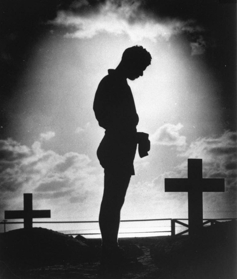 wehadfacesthen:  A Coast Guardsman bowing in reverence over the marked graves of American soldiers who gave their lives to win a small atoll during World War II, 1944 via legrandcirque