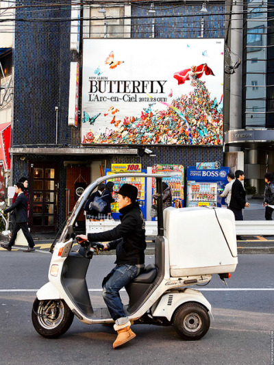 "L'Arc-en-Ciel ""Butterfly"" by tokyofashion on Flickr.A billboard for the upcoming L'Arc-en-Ciel album ""Butterfly"" in Harajuku. The little three-wheeled motorcycle in the foreground is a delivery vehicle. You see them everywhere in Tokyo."