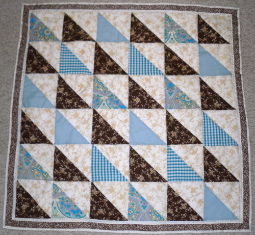 "This was completed today. It is another for the collection of baby quilts I am working on. I don't know how many counts as a 'collection'… four? five? Similarly to the post below this quilt measure 40"" square. I have quilted this simply along the lighter triangles and then around the border. The fabric used for the brown and cream triangles and brown border all came from the same duvet cover bought from a charity shop for £2.50! It was inspired by a Jane Brocket's Sample Book quilt from The Gentle Art of Quilting-Making."