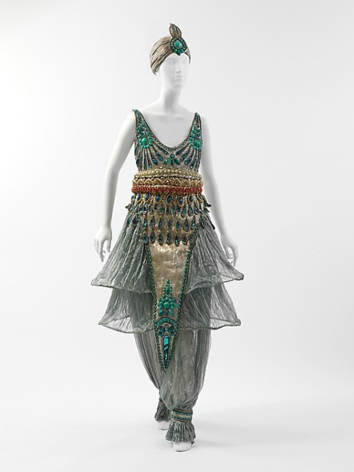 Fancy dress costume- Paul Poiret. 1911 The Met says: Early in the twentieth century Diaghilev's Russian dance company, Ballets Russes, performed in Paris—reigniting the taste for orientalism in Europe with its exotic sets and costumes. As this ensemble illustrates, Poiret excelled in recontextualizing western dress with fantastical eastern influence. He was also a maverick modernist in creating a stir, taking promotion of his inventive ensembles to new levels with his infamous spectaculars. This fancy-dress ensemble was made for and worn to Poiret's 1002nd Night party in 1911, which was designed and organized to promote his new creations in the full splendor and glamour of the orientalist trend