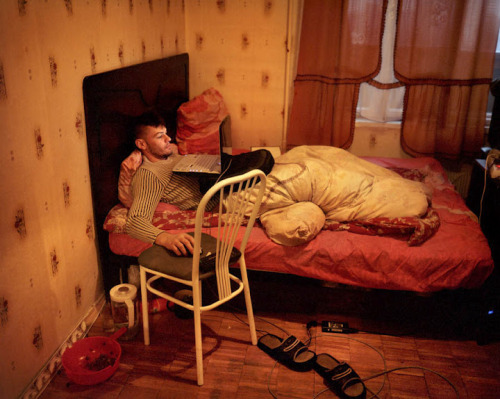 """I shot this picture of 28 year old Denis in his bed in Moscow. His main occupation is doing nothing. He used to work a lot as a young boy traveling all round Russia and Eastern Europe with her mother. He comes from Kazakhstan but has lived in Moscow since he was 11. He misses the Soviet times when people where closer one to another. Today everybody runs like crazy."" On a technical note Rafal remarked ""I try to shoot all my personal projects on film because it makes me calmer. I shoot digitally for my daily commercial and editorial work so when I have chance to shoot on film I do it with the greatest pleasure. Its another way of concentration and thinking. At least in my case. You have to think very carefully what you want to shoot if you have only 10 frames on film."" - Rafal Milach on Verve Photo"