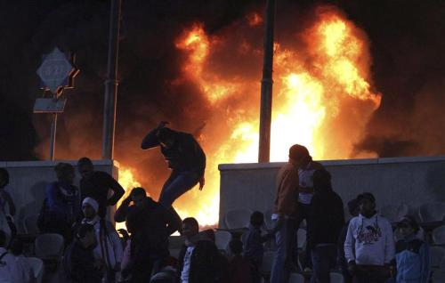 reuters:  A soccer fan flees from a fire at Cairo stadium, February, 1, 2012. [REUTERS/Stringer] Read more: Dozens die in Egypt soccer pitch invasion