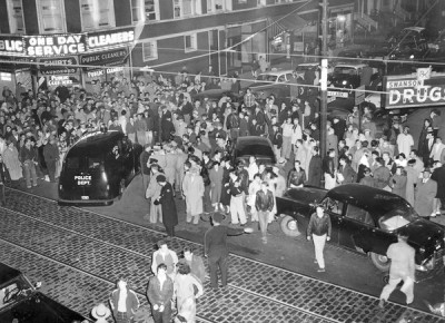 Corner of Clark and Berwyn streets in Andersonville, c.1954. A crowd has gathered after the capture and killing of a noted member of the mob.