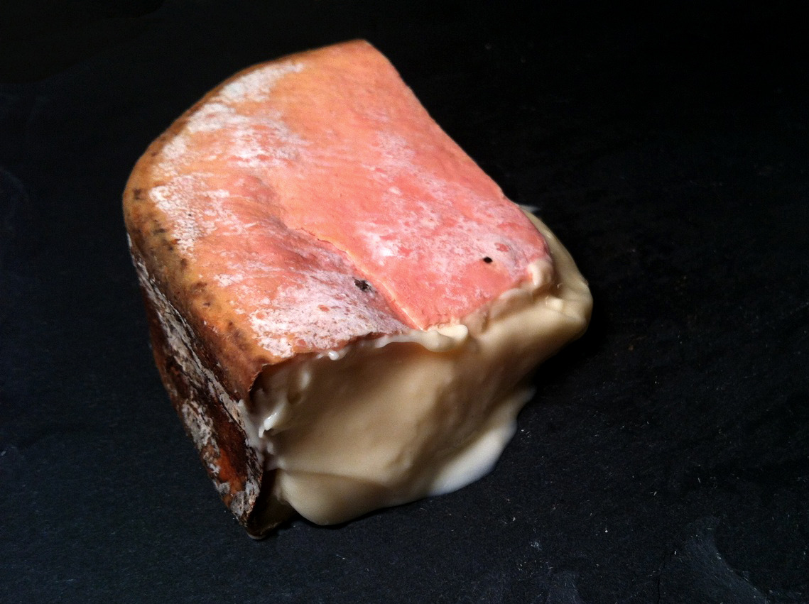 "A cheese that hardly needs introduction: Winnimere, from the Cellars at Jasper Hill, the cheesemaking and affinage masters behind Harbison (one of my cheeses of Christmas), Cabot Clothbound and many other notable American cheeses. Working with Herve Mons, they have created at the Cellars a first for America: a true French-style affinage facility, where cheeses can be developed, nurtured and aged to perfection, ""a network of seven underground vaults - a total of 22,000 square feet nestled beneath the pastures where Jasper Hill's forty Ayrshire cows graze. Each cave rests at distinct temperature and humidity levels, calibrated for different cheese styles."" As with all bark-wrapped cheeses, one would ideally buy a full wheel of Winnimere, lop the top off, and scoop the cheese out with a spoon. Unfortunately, when buying for one that can be a wee bit excessive, so I had to settle for this lovely wedge. Wrapped in spruce bark and washed with beer from a local brewery, the pink-rind holds in an oozing, buttery paste which collapses out of the cheese as soon as it warms to room temperature. Lightly stinky in aroma, in flavor it is a complex maelstrom of meatiness, sweetness, brine and grass with a lightly woody and smokey overtone from the bark."