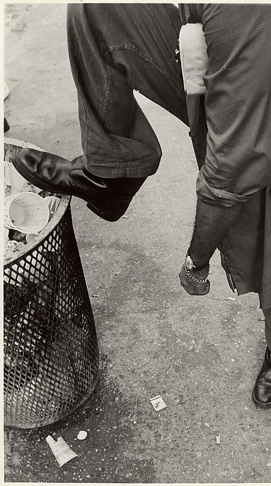 [Street Scene: Man Resting Foot on Lip of Trashcan, New York City] Leon Levinstein