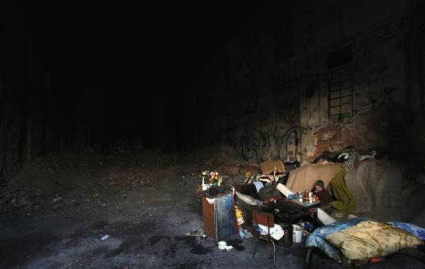Prague, Czech Republic A homeless woman sits in an abandoned factory which serves as a shelter for homeless people in the city's Vysocany district (via Reuters.com)