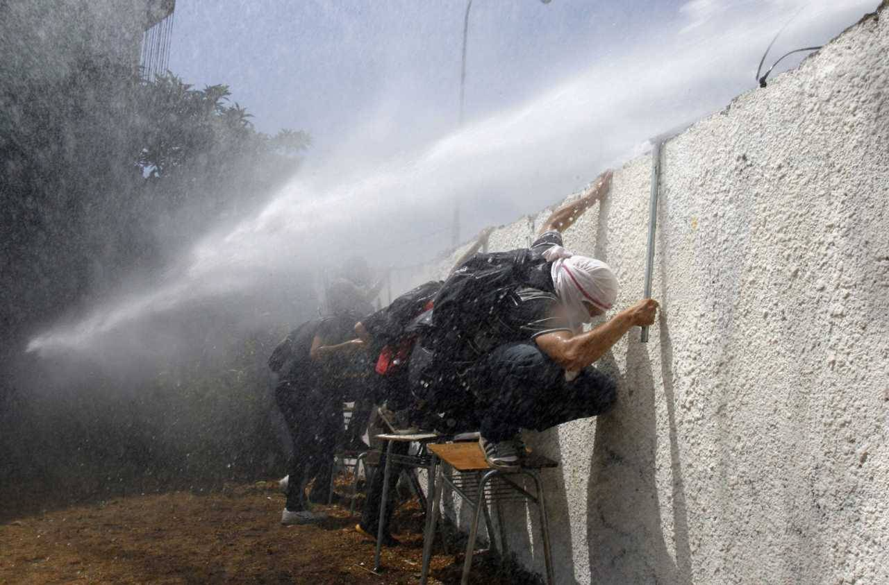 Students crouch behind a wall to hide from the water cannon truck during a demonstration against the government to demand changes in the public state education system in Santiago February 2, 2012. Chilean students have been protesting against what they say is profiteering in the state education system. [REUTERS/Victor Ruiz Caballero]