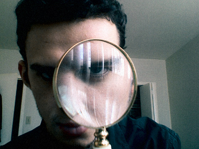 "Self Portrait Assignment:  The loupe is a symbol for my curiosity and fascination with details, otherwise ""little things"" that we usually are taught to ignore.  The reflection on the glass is the window of my room - I consider windows in general very inspirational and places for meditation. This image is a webcam capture, digitally cross processed (E6-C41) with a Fujichrome Velvia 100 Filter."