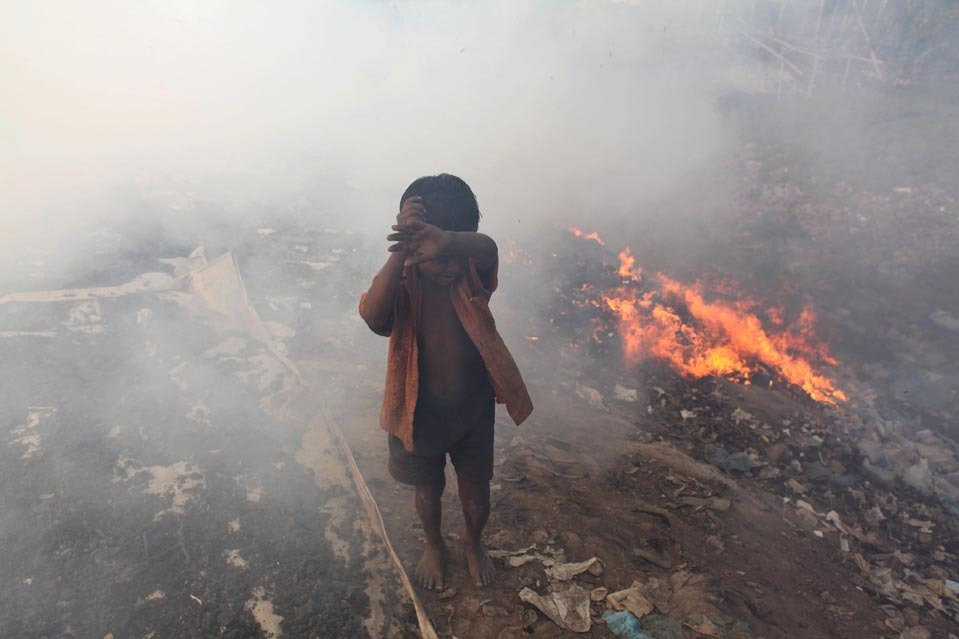 A child covered his eyes as he walked past burning trash in Dhaka, Bangladesh, Thursday. Acc