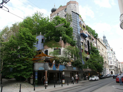 "The Hundertwasserhaus, designed by Friedensreich Hundertwasser, is an apartment block built from 1983-86 in Vienna, Austria. He wanted it to feel more natural and alive as he hated straight lines so the floors are all uneven, the roof is covered with earth and grass and large trees growing from inside the rooms, with limbs extending out the windows. The architect took no payment for the design of building, declaring that ""it was worth it to prevent something ugly from going up in its place"". He was an idealist, he wanted to turn the world away from cities, from grid plans and concrete jungles. The name was made to reflect those ideals ""Peace-kingdom Hundred-waters"".With a mix of apartments, offices, public and private terraces, a café and 250 trees and bushes it has become one of the most visited buildings in Vienna. Its vision has become an inspiration for other similar buildings that have since been built in the region"