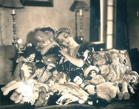 Alice White surrounded by dolls.