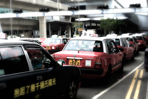 Red taxis line up at Hong Kong International airport on a cold grey day